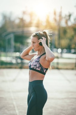 young woman runner athlete putting earphones during preparing to run
