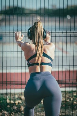 Rear view of young female runner doing stretching exercise on metal fence