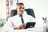 Spokojený africký podnikatel pracuje na digitálním tabletu v moderní kanceláři