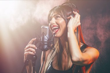 Close view portrait of young woman singer with headphones in front of microphone