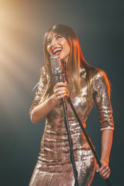 young woman singer in front of microphone singing with mouth wide open