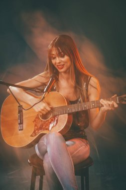 young smiling woman sitting and playing guitar