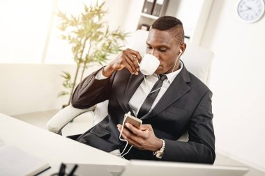 Young African businessman sitting in office and drinking coffee