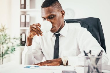Pensive African businessman drinking coffee and working in modern office
