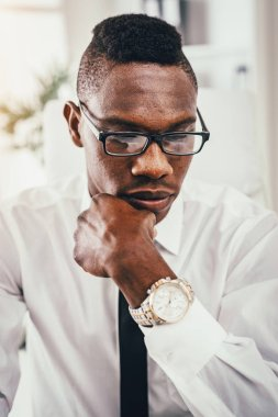 portrait of pensive African businessman working in modern office
