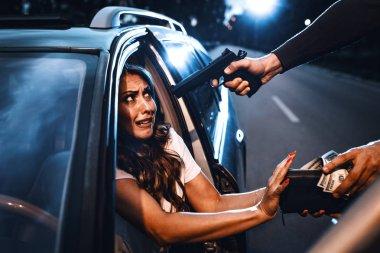 Bandit robbing shocked woman with gun in car