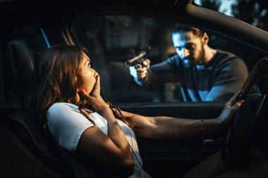 Dangerous man robbing woman with gun in car