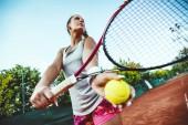 Fotografie Mladá tenisová hráčka, připravující se na tenis zápas