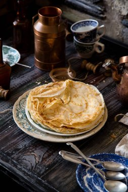 Homemade crepes on vintage plate with green ornament stand on rustic table
