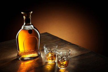 view of glasses of  bourbon  and a bottle aside on color background