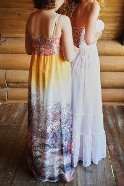 the bride is fastening a wedding dress.bridesmaid helps the bride .girlfriend helps bride