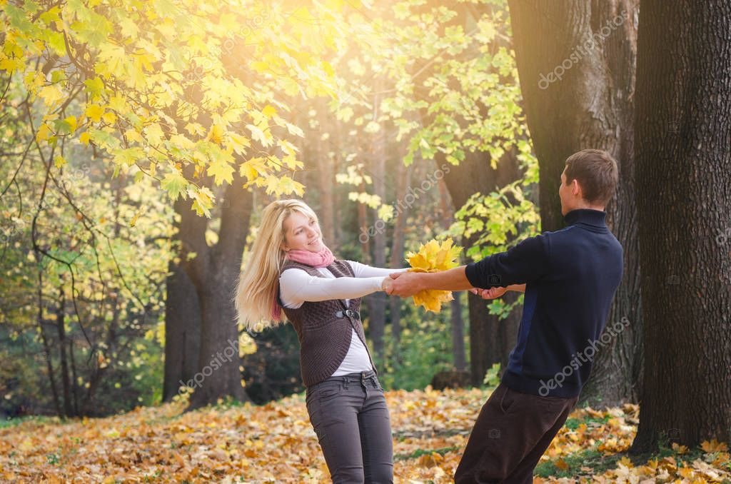 Loving couple is having fun. Walk in the autumn park