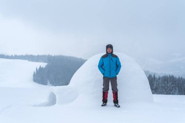 Eskimo igloo in the mountains. Winter adventures in the hike. Guy tourist in a down jacket