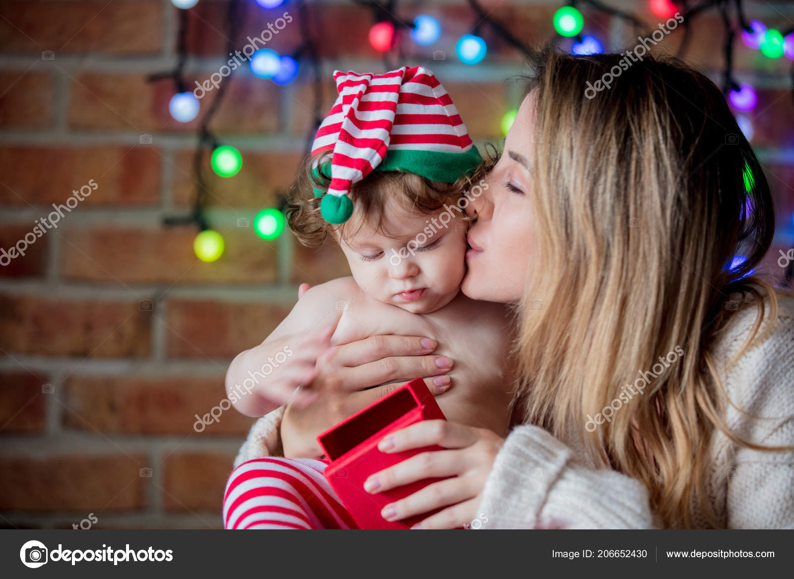 14ef4f2876c2a Beautiful little baby boy in elf hat and mother with fairy lights on  background. Christmas time season image — Photo by ...