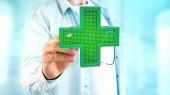 Fotografie View of a Businessman holding a Lighting pharmacy cross and a stethoscope - 3d render
