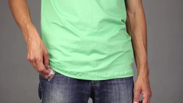 man in green shirt puts new condom in the front pocket of blue jeans, pats on the pocket and makes gesture thumb up, concept of relationships based on trust and responsibility, gray background