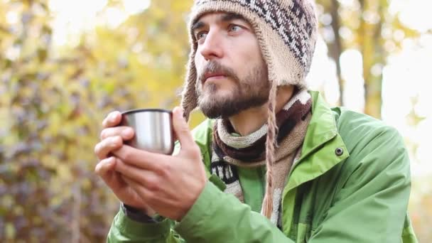 portrait of single bearded hipster millennial man warms his hands with cup of hot tea or coffee, dreams and think, side view, steam from mug, on the background of yellow autumn  forest