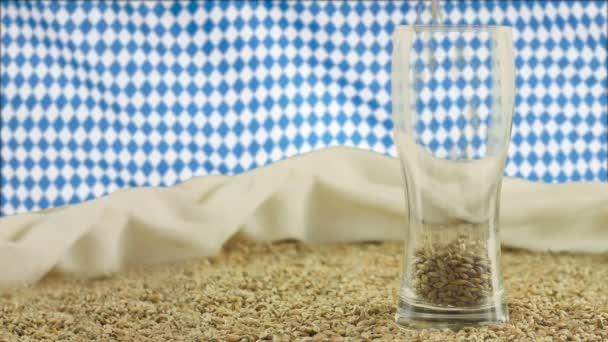 das konzept eines bierfestes in deutschland, ein bierglas vor dem hintergrund der bayerisch animierten fahne, in die malz gegossen wird, angebaut in einem sauberen gebiet