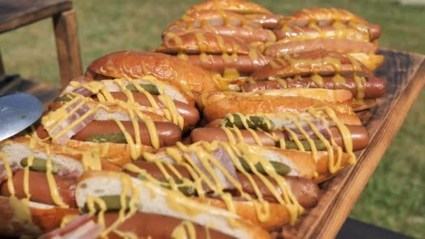 Háttere főtt hot dog hús kolbász, piros mártással, majonéz és a mustár a fa felületén a háttérben a zöld fű. Kamera mozgása 4k