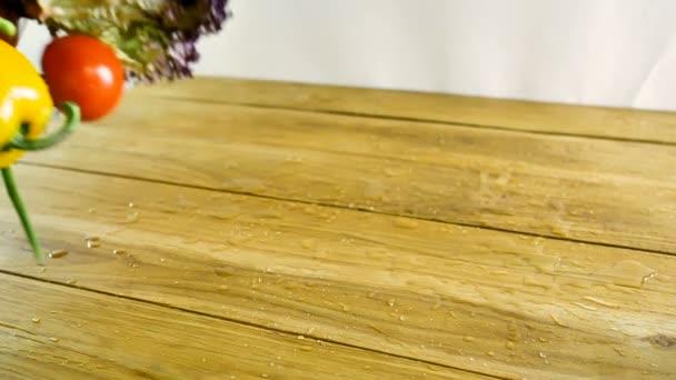 Výběr zahrnuje mrkev, brambory, okurky, rajčata, zelí, hlávkový salát, Beky, cibuli, česnek, ředkvička, Dill a petržel podávané na dřevěném stole v pomalém pohybu