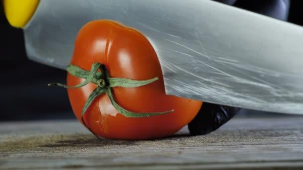 Proces uzavření červeného pepřového rajčete, šéfkuchař v černých rukavicích řezy rajských kroužků