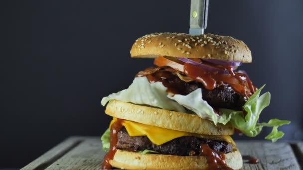 Velký burger s dvojitou zeleninovou zeleninou a sezamový Žička je držen společně s nožem vloženým shora a otáčí se v kruhu