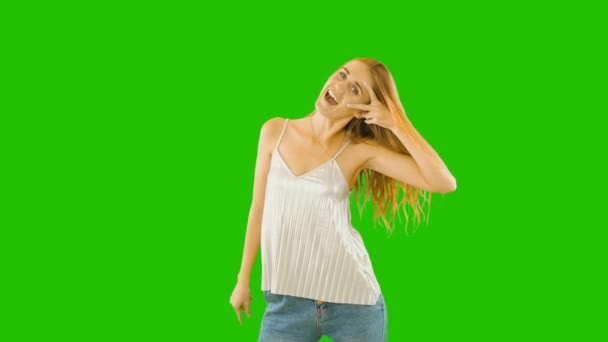 Cheerful cheerful girl with long hair shows her delight. Positive emotions. Holding two fingers near her eyes and smiling on a green background.