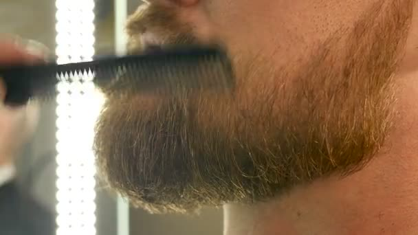 Master barbershop comfortably combing his beard and mustache for men preparing for a haircut, beauty salon for men