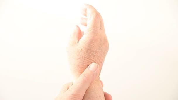 Muž flek a hýbe se svým bolestným zápěstí.