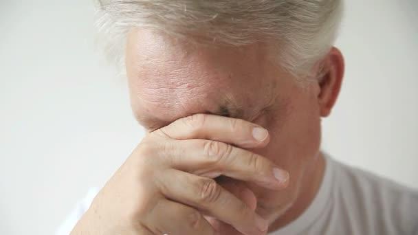 Starší muž vykazuje známky únavové a oční deště.