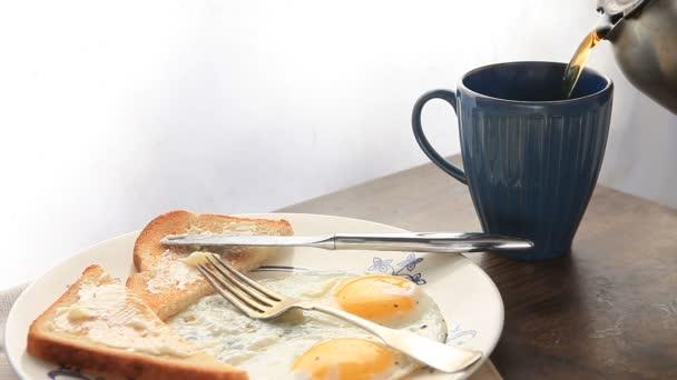 Kávét öntenek mellé egy tányér tükörtojás és pirítóssal