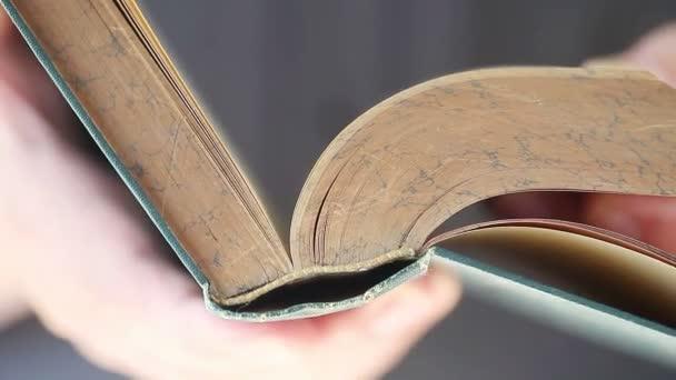Muž prolistí stránkami ve starožitně uzavíránkové knize
