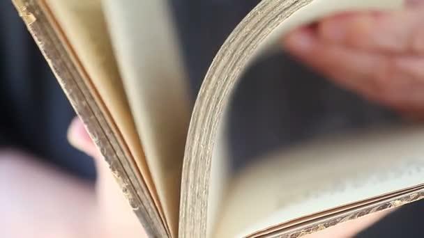 Egy férfi gyorsan ellenőrzi oldalakat egy régi könyv