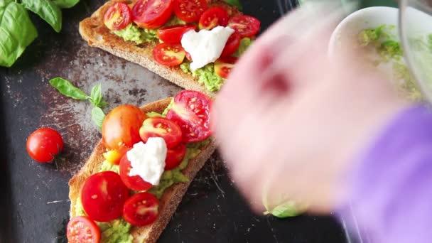 Žena umisťuje sýrový sýr a čerstvé bazalky na opékání avokáda a třešňová rajčata