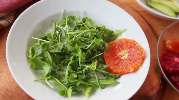 A woman adds fresh orange rounds and avocado slices to baby lettuces