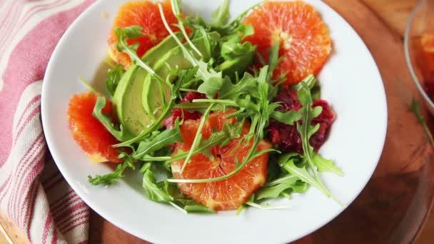 Egy nő tesz egy friss citrus saláta avokádó és baba zöldek