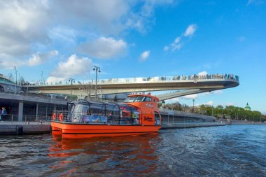 Moscow. Floating bridge in Zaryadye park over Embankment and River with pleasure boat