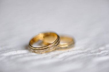 two wedding gold rings on white fabric