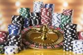 Fotografie Poker žetony na herní stůl, ruleta kolo v pohybu, kasino pozadí