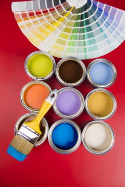 Buckets full of rainbow colored oil paint, red background stock vector