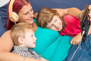 mother and sons with headphones listen to music hugging each other on the couch