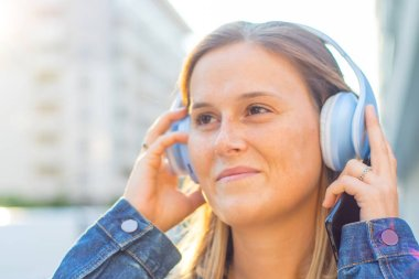 young smiling woman is listen music with headphone