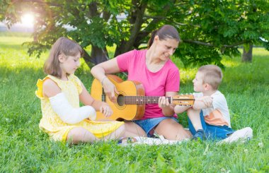 mom with her two children play guitar at the park. Relax and outdoor life concept