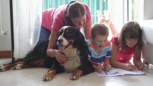 egy anya a gyermekével otthon rajzol, miközben kényeztetik a családi kutyát.