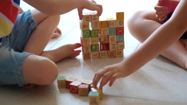 children are playing with generic wooden bricks on the floor at home