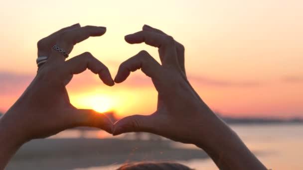 Silhouette Hände, die bei Sonnenuntergang eine Herzform formen
