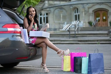 Young african woman is sitting on car trunk and looking at shoes she has just bought while phoning