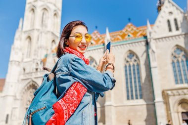 Asian hipster girl making photos on the smartphone in Budapest, Hungary