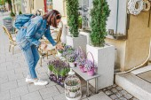 Photo A woman buyer selects and smells bouquets before buying at a flower shop on the street