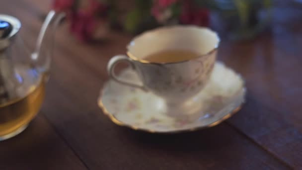 close-up footage of glass teapot and cup of tea on wooden tabletop with pink flowers